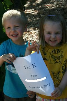 """Each year in Sept. I take a photo of the twins holding a sign with their school name and grade on it. Then in June I do the same thing. In the summer I frame the two 5""""x7"""" pics next to each other to create a super sweet way to remember these years that go by so fast."""