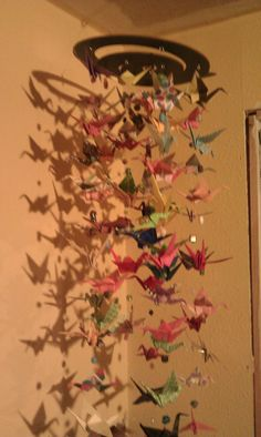 my kids and I made this paper crane mobile out of scrapbook paper, beads, and an old place mat super fun craft to do in the winter months
