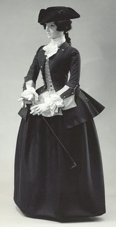 This is a perfect example of a riding habit. It has the mariner's cuffs and a poofy bottom to the jacket. The jacket is probably made out of wool. The mannequin is also wearing a tricorne hat which had a brim that formed gutters that drained the rain away. The standing collars were very common at this time after the 1760s.