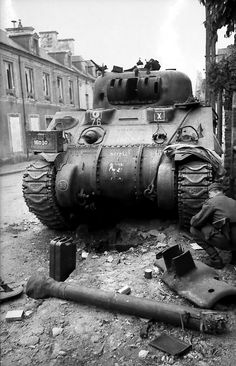 A German soldier inspects a destroyed Allied Sherman tank during the Battle of Villers-Bocage. The tank is likely one of many that SS-Obersturmführer Michael Wittmann destroyed. Wittmann is known for his ambush of elements of the British 7th Armoured...