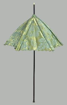 "Parasol, c1720. Green damask with large-scale floral design; cut scalloped edge; faded on top; straight black wooden handle with knob at end; ivory knob on top; said to have been made from ""Hannah Emerson's Wedding Dress, about 1720.