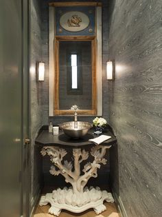 """POWDER ROOM:    Wallcovering: faux bois paper manufactured by Nobilis.     Mirror: 18th Century Directoire trumeau mirror from Regalo Antiques.     Base of sink: white plaster """"Branche"""" console from Myra Hoefer Design.     Pair of wall sconces: Thomas O'Brien for Circa Lighting."""