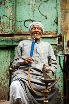 A smiling Egyptian man puffs on a waterpipe at a streetside cafe in Islamic Cairo, Egypt.