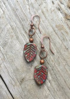 """Small, rustic red Czech glass leaves with antiqued copper. Approx 1.5"""" in length and light weight."""