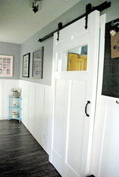 hallway with diy wainscoting and a white barn door made for the space. Rustic feel, dark gray walls, black hardware make the barn door pop. To see more visit- http://ourhousenowahome.com/