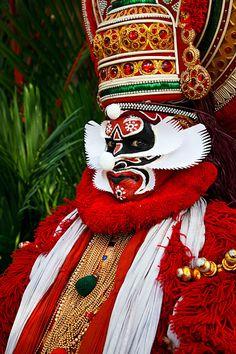 Portrait of Kathakali dancer in full make-up and costume portraying Chuvanna Thadi, wearing elaborate headgear called Mudis