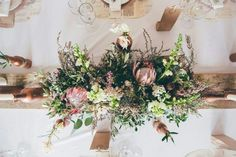 Hints of raw wood on the tables gives a warm vintage feeling together with the Cape fynbos.  I used wooden runners and made wooden boxes for my flowers