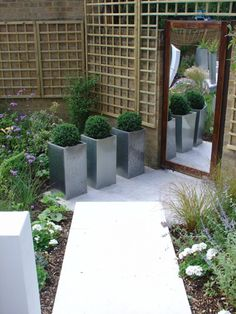 Beautifully cut white granite paving combines with white rendered walls to reflect light and make this small garden feel much larger.