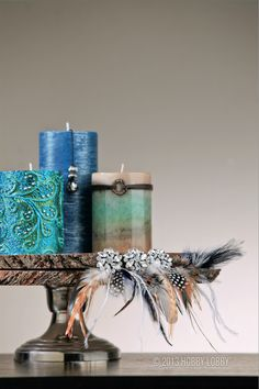 To create this eye-catching centerpiece, hot glue an assortment of feathers and dazzling jewels to two wood slices and top with your favorite pillar candles!