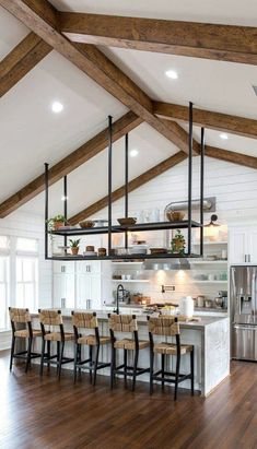 Open concept kitchen with vaulted ceilings, exposed beams and hanging steel open shelving
