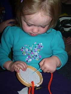 Great idea for teaching a little one to sew. Embroidery hoop and shelf liner/rug pad.