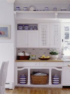 Blue and white Cornish-style kitchenware looking fantastic in this pristine white modern country kitchen. With complementary tiling, natural accessories, blonde wood work surface and floor, the whole look is bright, contemporary and very easy on the eye