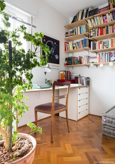 Home Office integrado à sala de apartamento compacto tem bancada de madeira revestida com fórmica e prateleiras para livros.