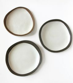 """Shallow dishes made by layering brown stoneware on top of white. The inside is glazed with a food-safe satin white, and the rim and exterior are left unglazed. Red-brown edge dish: approximately 8"""" in diameter, $55 Dark brown edge dishes: approximately 8.5"""" in diameter, $65"""