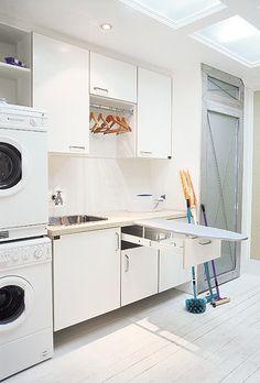 Lavanderia esteticamente integrada aos outros ambientes da residência. A porta de acesso é de aço escovado e vidro jateado. Armários com espaço para a roupa suja, a limpa e a passada. A tábua de passar dobrável fica armazenada em uma gaveta