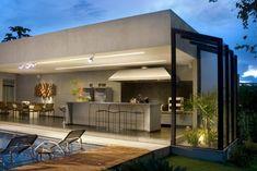 """Área de lazer tipo """"clean"""" com piscina e área de churrasqueira/bar em materiais sofisticados."""
