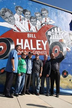 """Mayor Ernie Troiano Jr.; Comets Joe D'Ambrosio and Dick Richards; Commissioners Tony Leonetti and Pete Byron; and Jon """"Bowzer"""" Bauman of Sha Na Na stand in front of the new mural Friday, Oct. 17."""