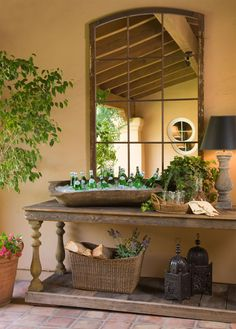 This outdoor veranda features pieces originally used in an interior setting. The large antique potting table is a perfect addition for outdoor entertaining.