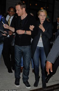That's what co-stars are for! Kate Winslet kept a tight hold of Michael Fassbender's arm as they were mobbed by fans while leaving a New York hotel on Sunday night