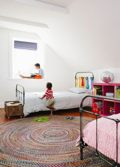 The kids' room features a pair of iron beds from Pottery Barn, a rug by Dash & Albert, and a pink bookcase from IKEA. | Lonny.com