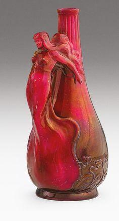 Zsolnay szecessziós díszváza  Formába öntött fehércserép, alján reliefszerű magyaros szecessziós virágdekor. Felületén részben savmaratott, többrétegű, színes eozinmázakkal festett.   Feltehetően Mack Lajos formaterve.   Felületén apróbb karcok és kopások.   Alján jelzett: masszába nyomott 8580 (formaszám)   és vörös eozinmázzal festett kerek, domborodó, pecsétszerű márkajelzés.   Zsolnay, Pécs, 1910 körül.   M.: 24,7 cm BA17/280e