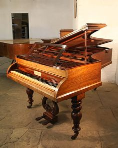 An 1835, William Stodart grand piano with a rosewood case. Piano features carved piano lyre and baluster legs. Keyboard has a cylinder roll top fall at Besbrode Pianos. Metal tubes were introduced by the Stodarts to strengthen the frame.