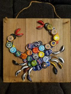 Approximately 12 x 12 inch wood with bottle cap crab. Beer cap brands may vary. Approximately 12 x 12 inch wood with bottle cap crab. Beer cap brands may vary. Beer Cap Art, Beer Bottle Caps, Bottle Cap Art, Beer Caps, Bottle Cap Coasters, Bottle Stopper, Seashell Crafts, Beach Crafts, Beach Themed Crafts