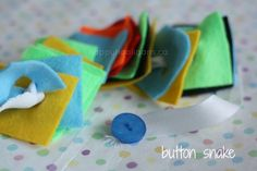 Attach a button to each end of a piece of ribbon. Cut out felt shapes with a slit through the middle of each. Have the child thread the ribbon through the slits to create a snake of felt.