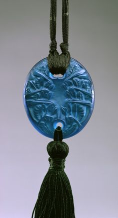 René Lalique (French, 1860-1945)  Blue Oval Pendant with Wasps (Guepes), moulded glass, silk cord, 1920