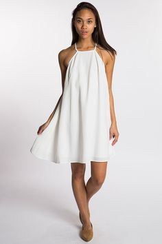 white a-line dress with a halter neck. made by the fifth label.