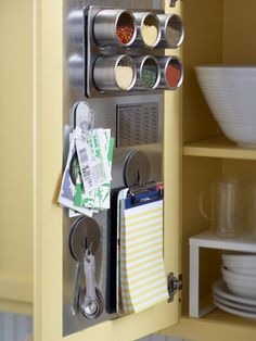 Take advantage of the inside of cabinet doors. A sheet metal insert turns the interior door panel into a handy storage system with the addition of magnetic hooks, clips, and containers. Keep a notepad handy to jot down anything you need to purchase at the grocery store.  www.bhg.com