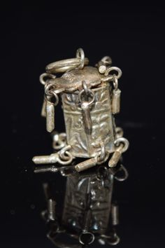 """This tiny vintage charm is absolutely stunning. The silver lantern is jam packed with detail! There is a 3D body, tiny moving parts, and pictures on each panel.  The top is stamped Silver Can be worn on a charm bracelet or as a pendant on a necklace.  Aprox 2.3 Grams Aprox 6/8"""" tall"""