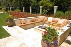 Travertine patio with raised planters and pots creates drama and sunken lounge seating around a fire pit creates an intimate space for outdoor parties.