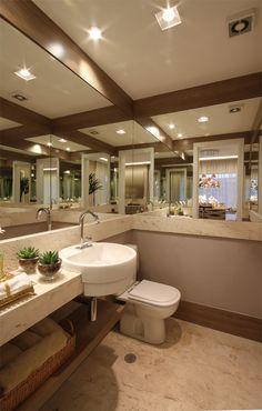 O lavabo ganha charme e elegância ao trabalhar com tons neutros e adornos delicados. Porém, um detalhe marcante foi a composição do jogo de espelhos com a madeira, que passou imponência e conforto  para o ambiente http://ow.ly/dBMJ4