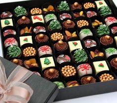 Essa é a caixa premium com 64 bombons decorados em 7 sabores: mini árvore trufada, presentinho de camafeu de nozes, bombom de maracujá, mediant de frutas secas, brigadeiro chic dourado, copinho de Nutella e bombom de damasco. Os mesmos doces podem vir em caixas menores de 20 unidades.