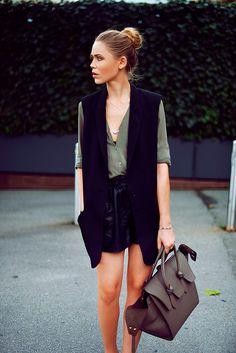 Foto se street style com look básico de camisa verde militar, maxi colete preto e shorts de couro preto