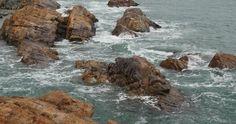 4k sparkling ocean sea water waves surface & coastal rock reef coast surge shore.