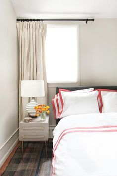 Get ready to relax in this restful bedroom featuring a bed dressed in a red border duvet with matching shams positioned in front of a black headboard located under a window covered in cream curtains hung behind a gold and gray nightstand lit by a white and gray striped lamp.