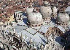 """Basilica di San Marco; Venezia; XI-XIV secolo. Vista dall'alto.   La basilica presenta una pianta centrale a croce greca; dall'esterno, è facilmente riconoscibile la presenza del marmo, che era stato letteralmente """"staccato"""" dai muri di Costantinopoli dopo che la città era stata saccheggiata. Tale ri-uso architettonico, aveva un valore fortemente ideologico, che evidenziava il modo in cui la città avversaria era stata messa in ginocchio."""