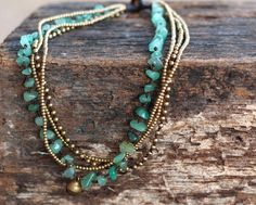 This necklace made with jade stones, brass beads woven together with dark brown wax cord and brass bell for closure