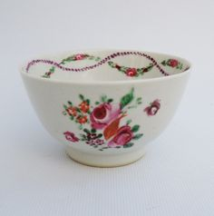 """A fine 1700's Chinese export porcelain tea bowl with rose floral pattern and roses swags to the interior interlaced by  a purple rope. All hand painted;  Very nice translucence.  Just shy of 2"""" high with a top diameter of 3 1/2""""."""