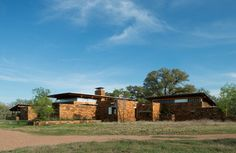 Constructed of durable, rugged materials appropriate for a ranch, Big Tree Camp is anchored by its Texas-quarried sandstone north wall. Rust-colored like the sandy soil, the wall appears to grow from the earth and acts as a wind break in winter months. Strips of clerestory windows peer over the stone and allow indirect light into the long one room deep dwelling. Specific portals in the wall give glimpses of the field to the north.