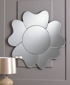 This beautiful circular mirror is in the form of a single flower, the round centre being surrounded by five large curved petals. This mirror would makes a stylish addition to any home.