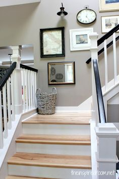 Staircase Makeover! Hickory Wood Floors, Black and white railing, new lights and gallery wall. i like the grey/brown wall color..but it might be too dark for our stairs where there is no skylight.