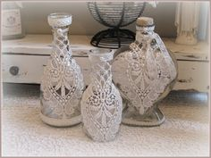 Glass bottles, decorated with antique lace, ribbons and pearls.