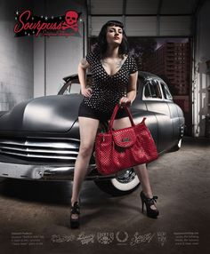"""CLASSY DAME PURSE RED    Price:$52.00    Made by Sourpuss    Strut your stuff like you own the place with our Classy Dame purse! This shiny red """"studded"""" vinyl purse has magnetic closure, """"Sourpuss"""" hardware, circular metal feet, sturdy handles, zip top with lightning bolt pull, built in mirror & leopard print lining.  18"""" by 12"""" by 5"""""""