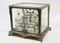BACCARAT Magnífico tântalos em bronze ormolu com cristal composto por quatro garrafas e 11 cálices