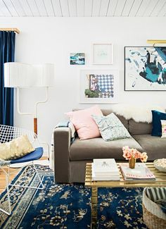 Emily Henderson's living room, from Domino, has a palette of blue, beige, and white, with subtle accents of light pink and gold.