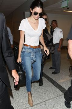 Jenner utilizes an easy and quintessential '90s styling trick by tying a plaid flannel around her high-waisted jeans.   - MarieClaire.com