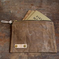 """This is the Waxed Canvas Field Notes Pouch by Old Church Works. You are a Field Notes or Moleskine carrying creative, right? You have your notebooks filled with creative treasures, wrapped in Old church Works Leather, but now you see something to keep them all together. Approximately 5"""" x 7"""" 12 oz. Duck Canvas hand waxed with natural bees wax. Solid brass zipper. Solid brass rivets. Natural vegetable tanned leather zipper strap. Perfect for your Field Notes."""